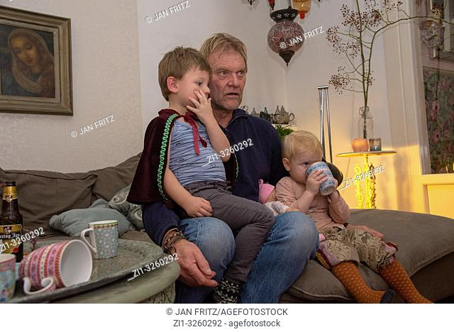 grandfather with grandchildren watching tv