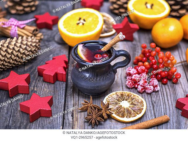 mulled wine in a brown ceramic mug on a gray wooden background, beside ingredients and Christmas decor