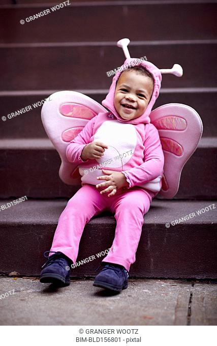 Mixed race girl wearing pink butterfly Halloween costume on staircase