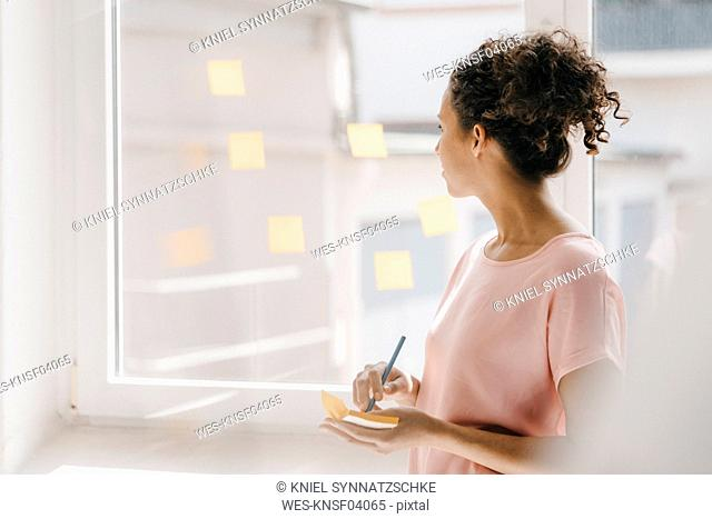 Woman posting adhesive notes on window, brainstorming