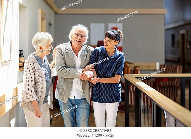 Gereatric nurse helping senior man and woman to walk down corridor