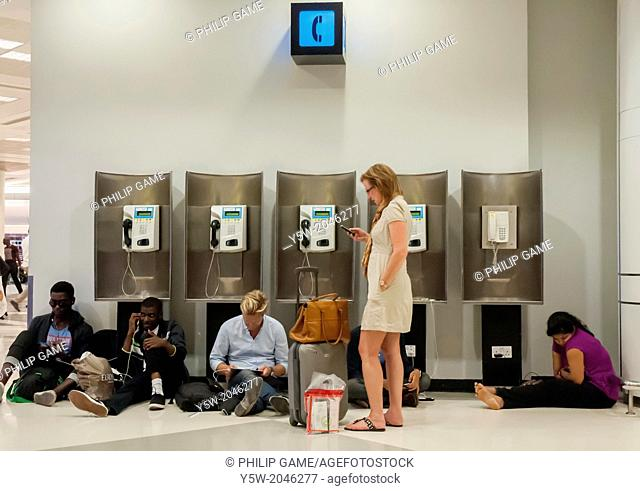 Passengers at Doha Airport, Qatar, use smart devices whilst ignoring a bank of payphones
