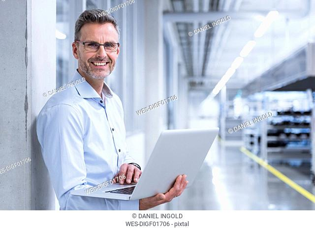 Manager on shop floor of factory using laptop