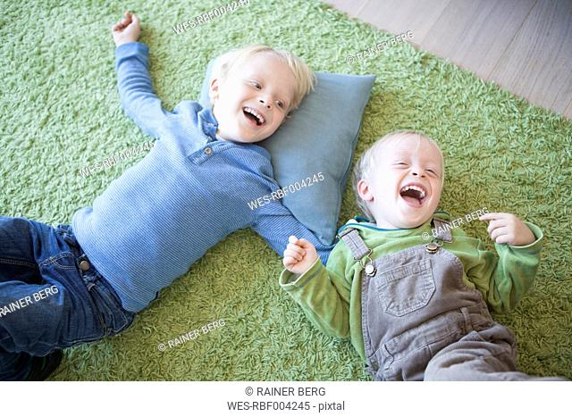 two laughing little brothers lying on green carpet at home