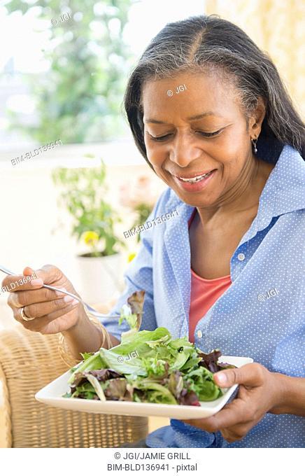 Mixed race woman eating salad on sofa