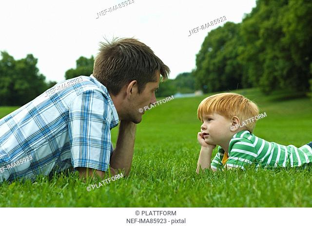 Father and son lying on lawn in park
