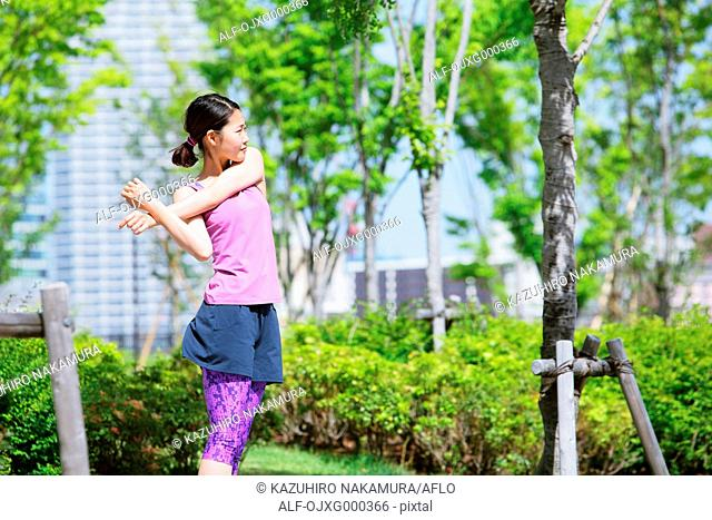 Young Japanese woman stretching before her run downtown Tokyo