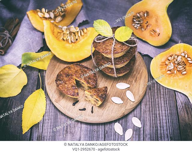 cooked cupcakes of pumpkin on a wooden board, next to fresh pieces of pumpkin