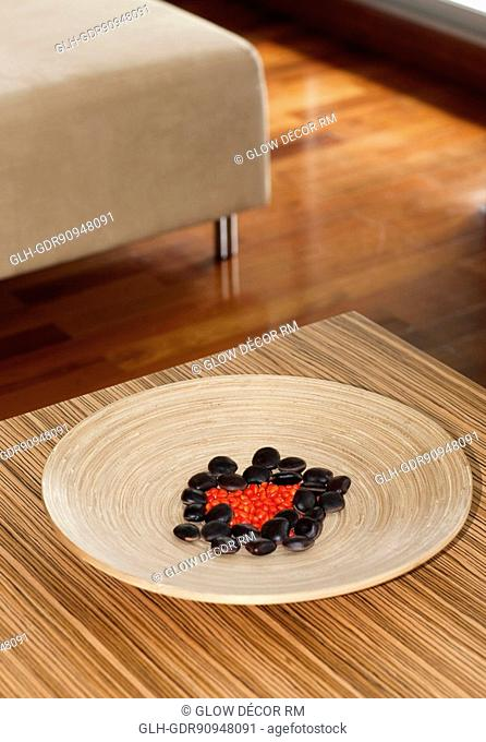 Pebbles in a wooden plate on a table