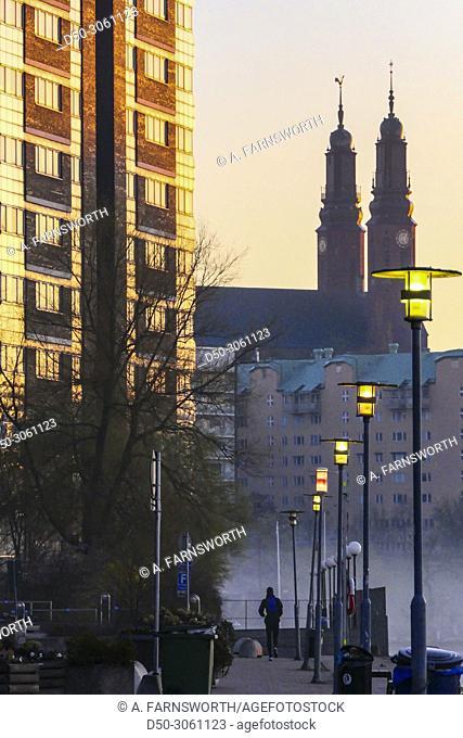 Stockholm, Sweden Jogger at dawn with fog in the neighborhood of Liljeholmskajen and Marievik