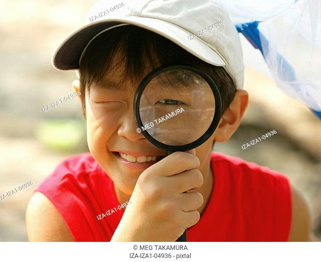 Close-up of a boy looking through a magnifying glass and smiling