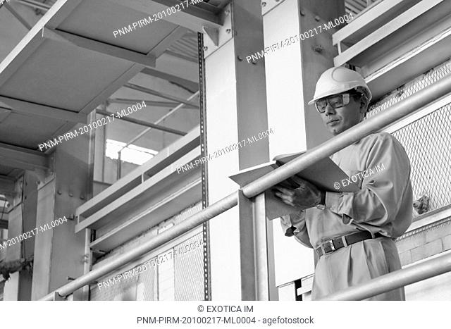 Engineer holding a notebook in a factory, Surya Roshni Limited, Gwalior, Madhya Pradesh, India