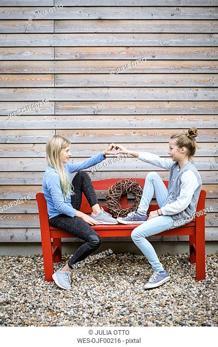 Two best friends sitting on a red bench in front of a wooden facade forming heart with their hands
