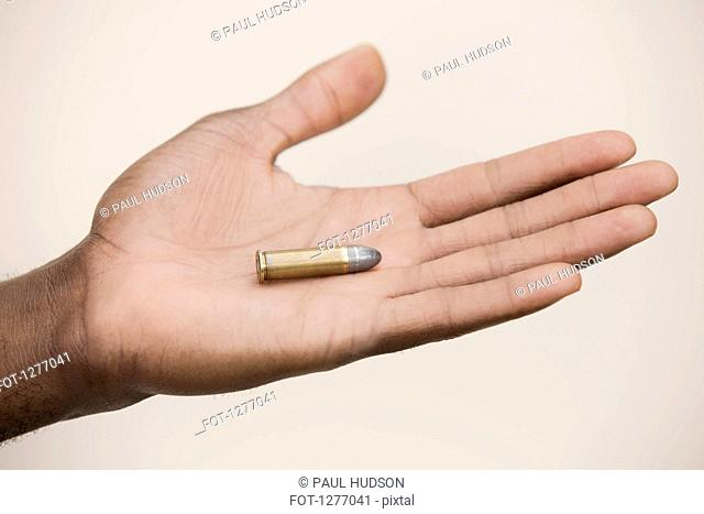 Man holding out a single bullet