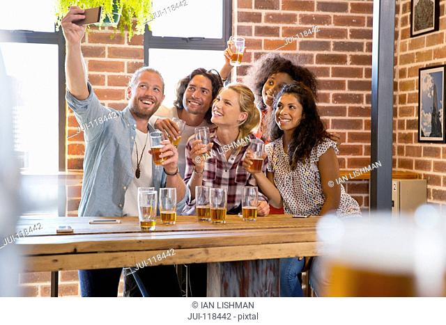 Group Of Friends In Bar Posing For Selfie On Mobile Phone