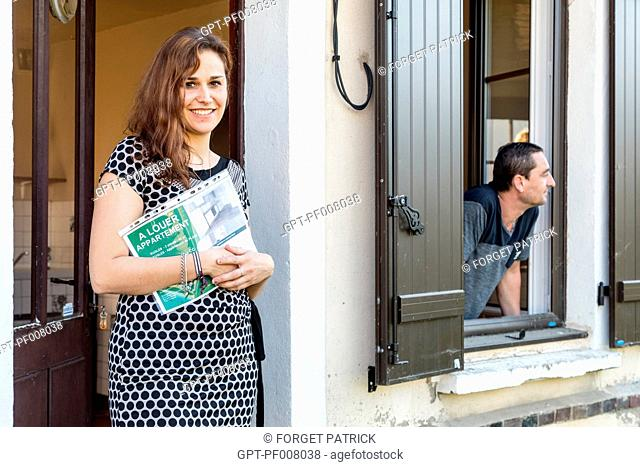 REAL ESTATE AGENT WITH HER CLIENT VISITING A HOUSE FOR RENT IN THE CITY, RUGLES, NORMANDY, FRANCE