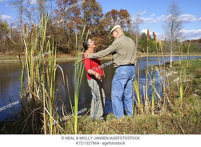 Elderly couple stand talking and laughing by a lake