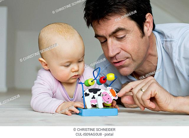 Mature man and baby daughter playing with toy cow