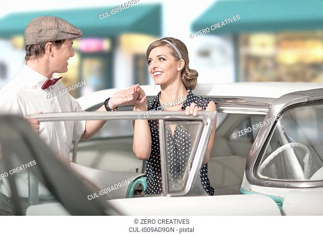 Man helping woman out of vintage car