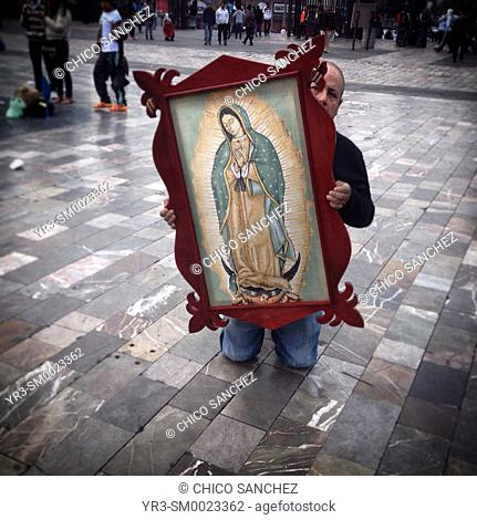 A man holding an image of the Virgin of Guadalupe walks in his knees during the annual pilgrimage to the Our Lady of Guadalupe basilica in Mexico City, Mexico