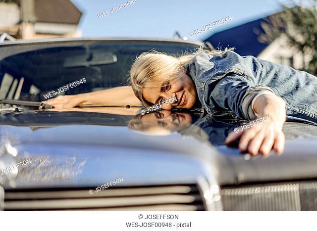 Woman lying on her car