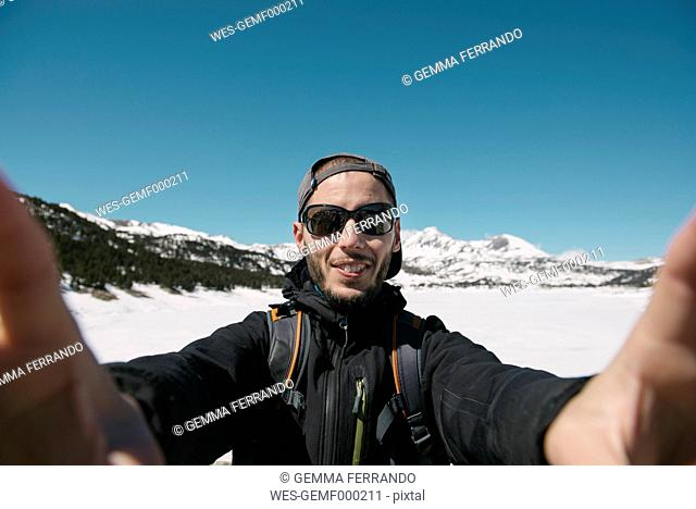 Spain, Catalonia, man taking a selfie in the mountains with frozen Lac des Bouillouses in the background