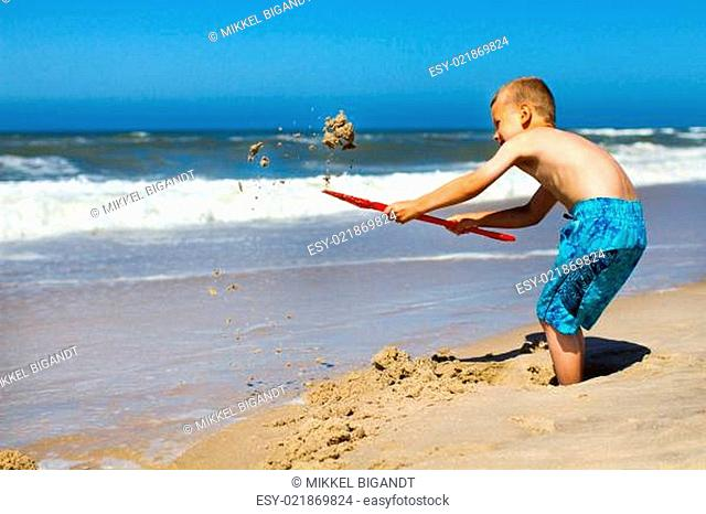 Boy digging a hole at the beach