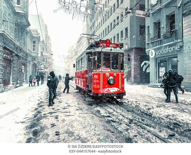 Winter view of nostalgic red Tram and people in daily life while snowing at popular Istiklal Street of Beyoglu,Istanbul,Turkey. 07 January 2017