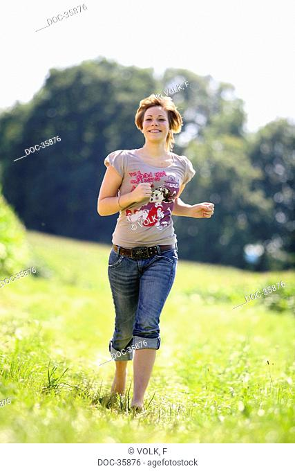 Young woman runs laughing towards the camera - meadow in the background