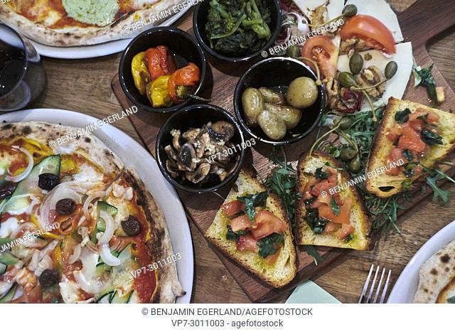 starter with bruschetta, bread, rucola and baked potatoes in olive oil between fresh pizzas in a Neapolitan restaurant