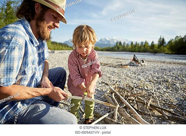 Mid adult man and boy using pocket knife to remove bark from branch, Wallgau, Bavaria, Germany