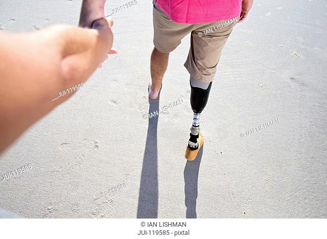 Point Of View Shot Of Man With Artificial Leg Walking Along Beach Holding Hands With Female Partner On Summer Vacation