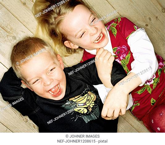 Boy and girl lying on floor and laughing