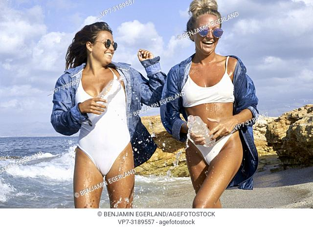Two women playing in sea water at beach, Chersonissos, Crete, Greece