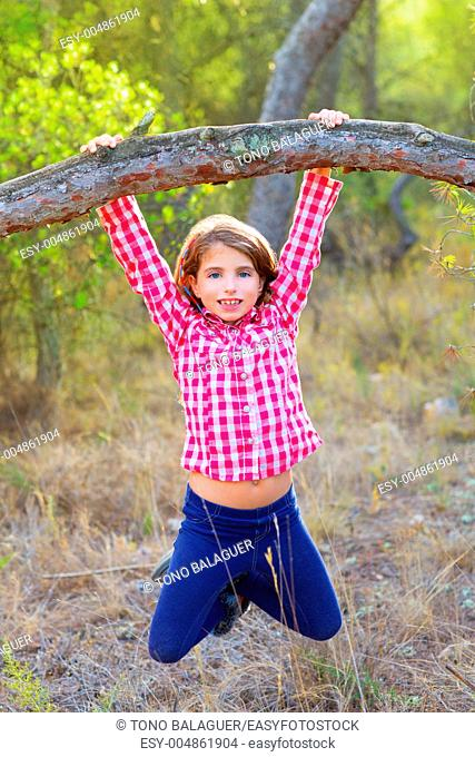 children girl swinging in a tree trunk in a pine forest