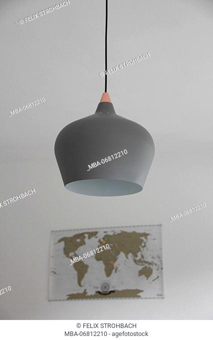 Pendant light in grey with a map of the world in the background