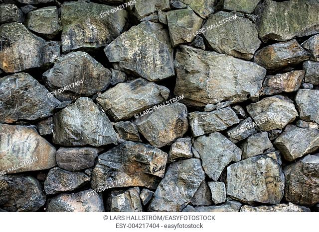 Surface of natural rock tiled into solid wall with nice texture