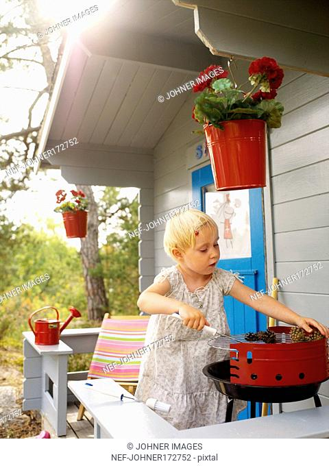 Girl barbequing on the porch of a playhouse