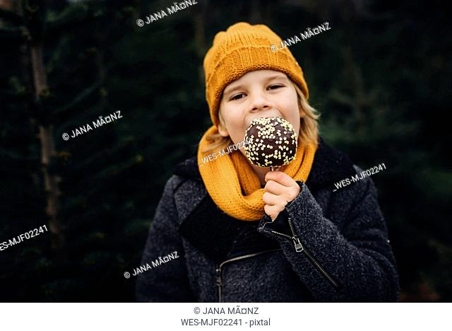 Little boy standing in front of fir trees, eating chocolate dipped apple