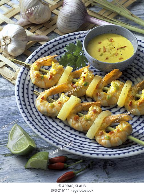 Shrimp kebabs with pineapple and dip on plate