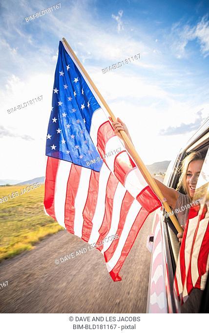 Hispanic woman waving American flag out car window