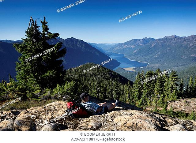 A lone hiker takes a break on the Flower Ridge trail overlooking Buttle Lake in Strathcona Park, Strathcona Park, Central Vancouver Island, British Columbia