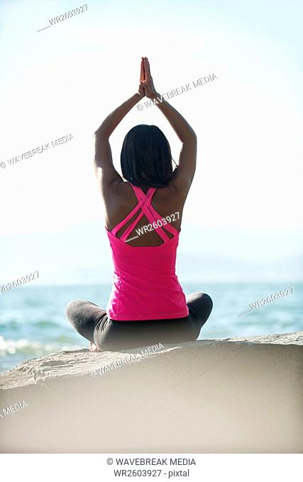 Rear view of woman performing yoga on rock