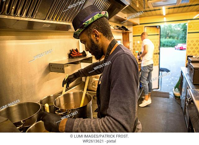 Two men cooking in commercial kitchen of food truck