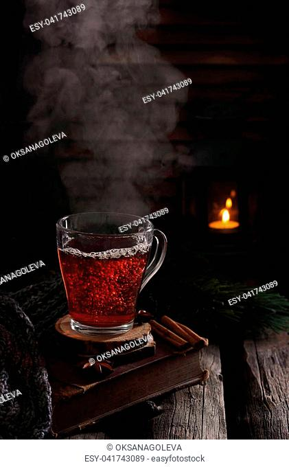 cup of hot boiling black tea in winter scenery, natural smoke