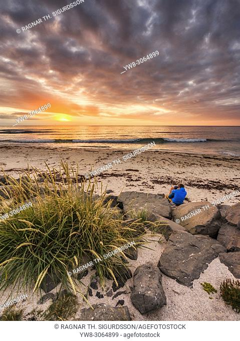 Couple at the beach at sunset, Latrabjarg, West Fjords, Iceland