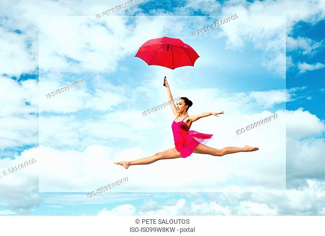 Ballerina with umbrella, leaping against cloudy sky