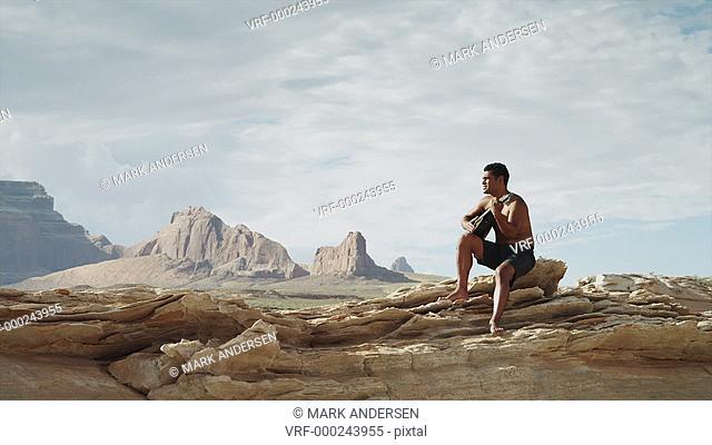 WS DS Man playing guitar on rocks near Lake Powell / Utah, USA