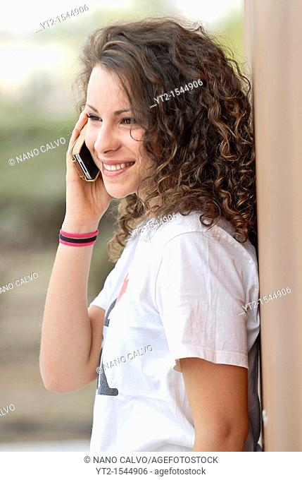 Cute teen talking with her mobile phone