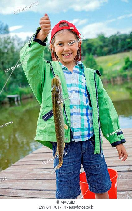 Happy cute boy enjoyed the fishing. Holding a big pike